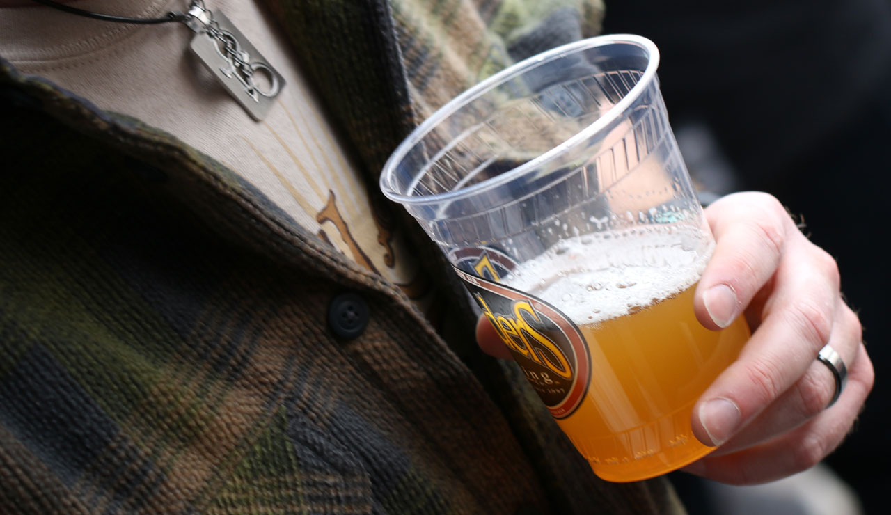 Close up of a person holding a plastic Founders cup with beer
