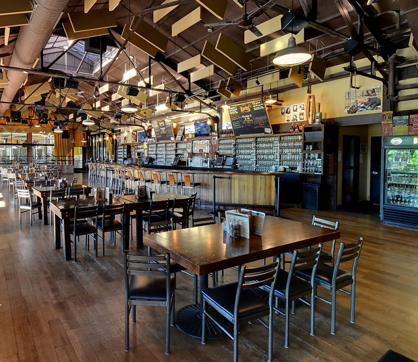 Founders Grand Rapids taproom showing tables and chairs and the bar to the right
