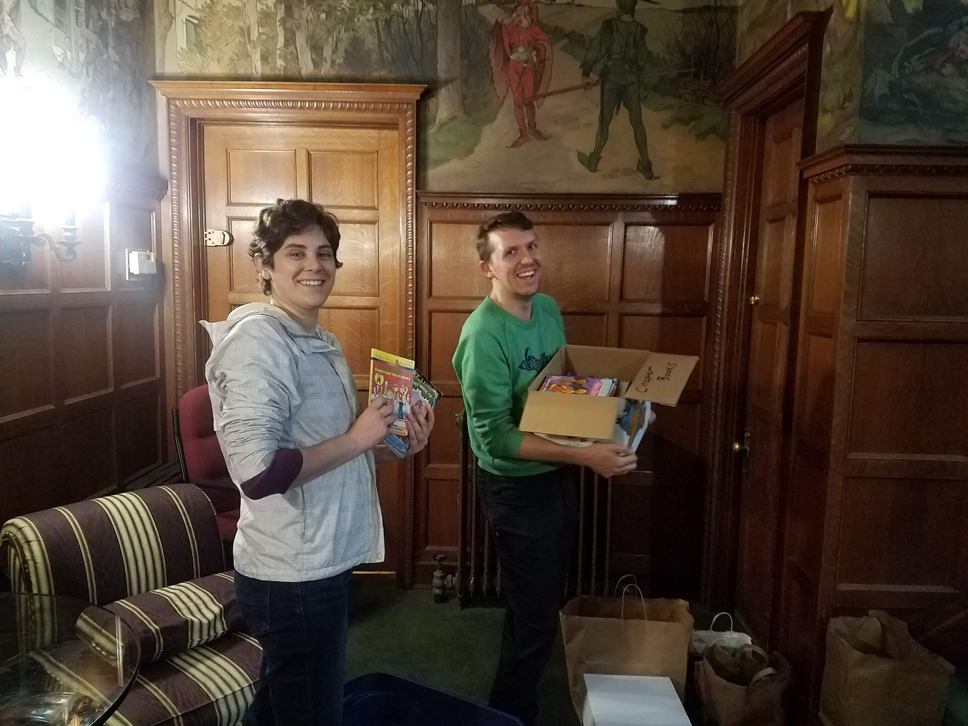 Two people with books in their hands smiling