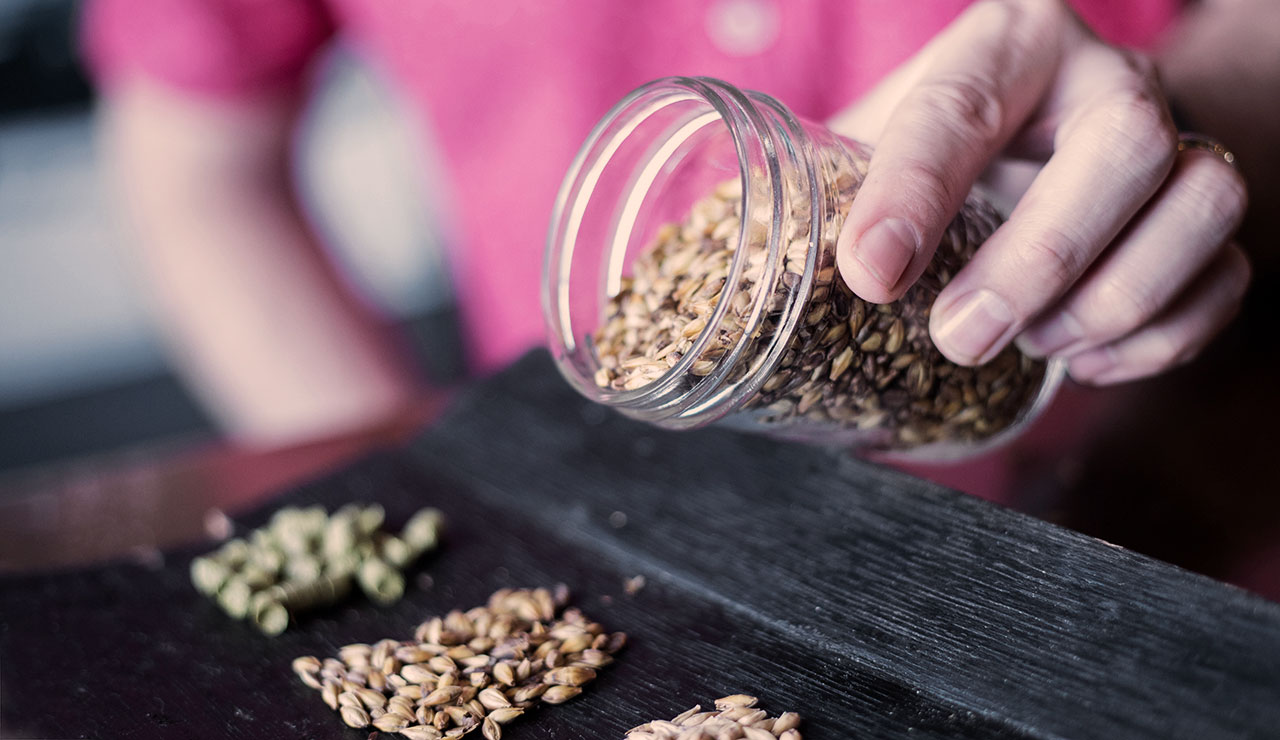 Person dumping seeds out of a glass jar