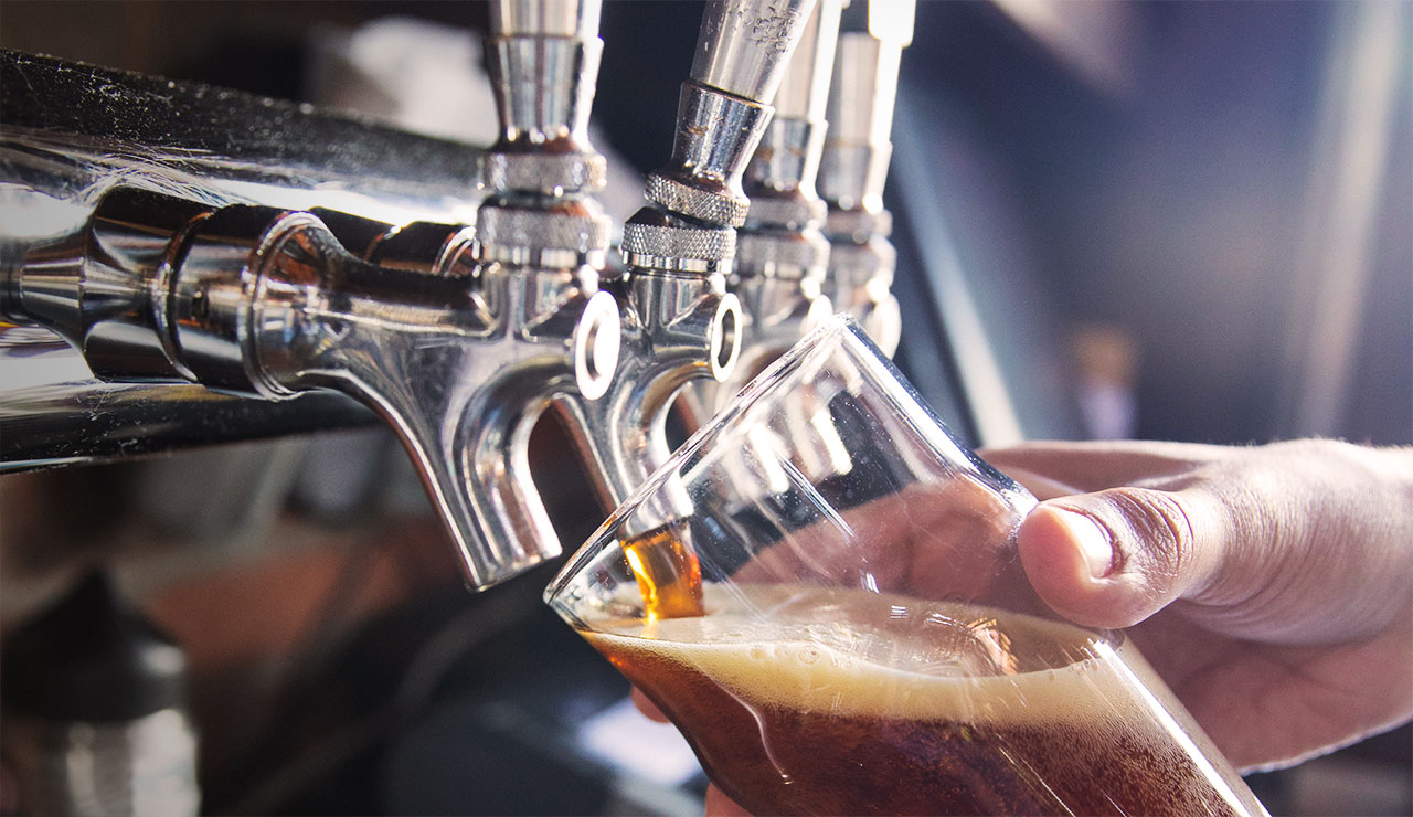 Close up of man pouring a draft beer