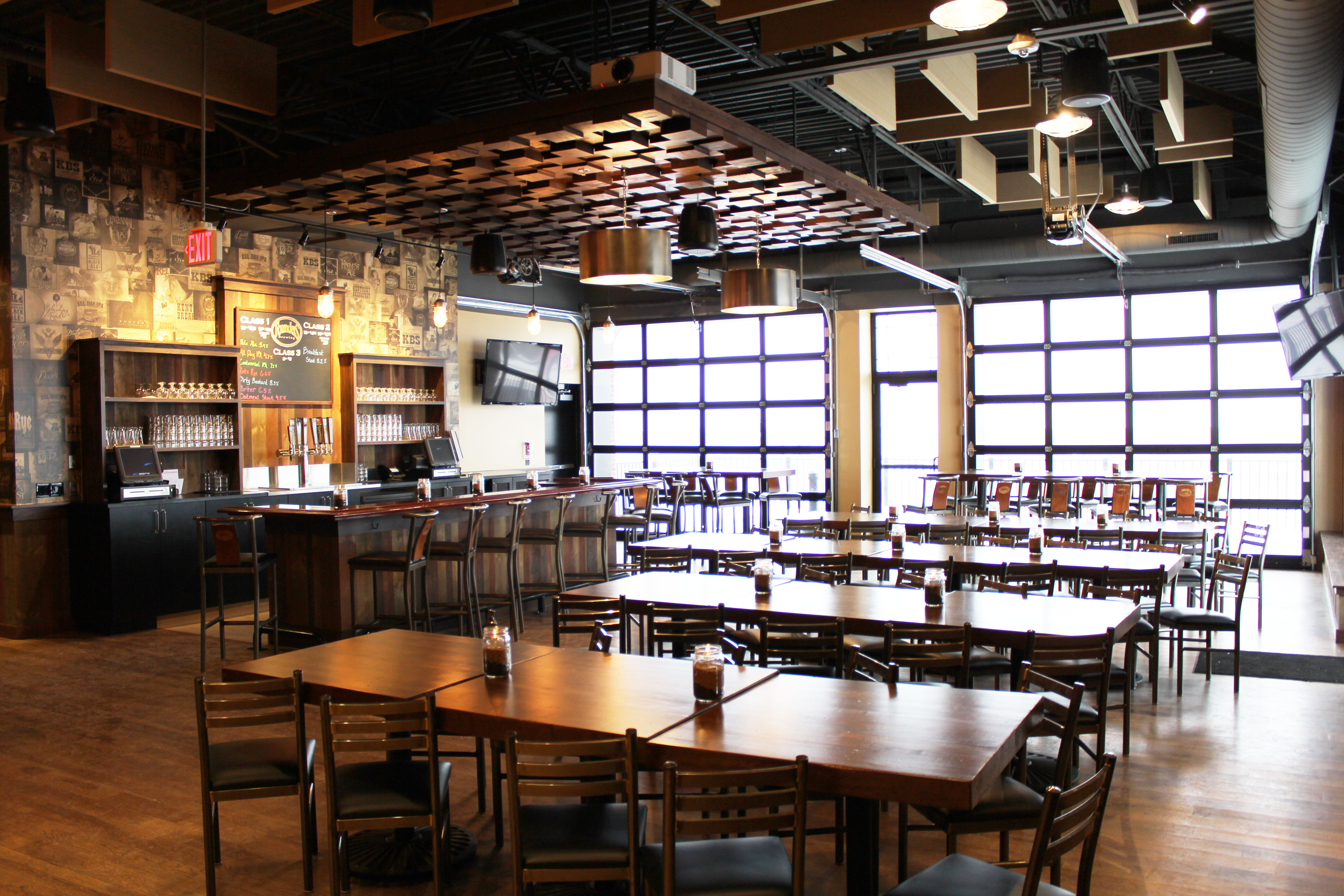 The Centennial Room view with tables and chairs facing windowed garage doors