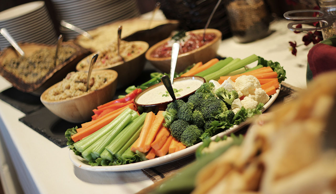 Table with a veggie tray, dips, salsas and plates