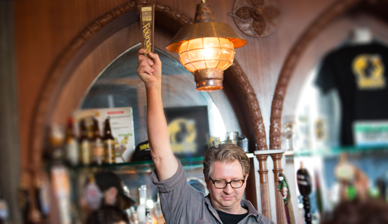 Man holding up a Founders tap handle in the bar