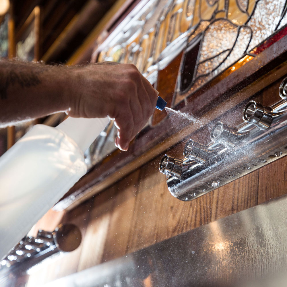 Man spraying water on draft lines at Founders Brewing Co.