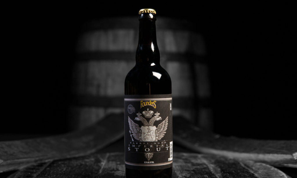 black and white barrel-aged imperial stout bottle positioned on bourbon barrels