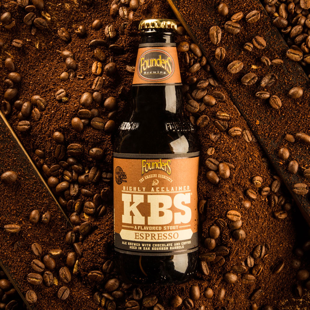 kbs espresso bottle laying on coffee beans and bourbon barrel staves