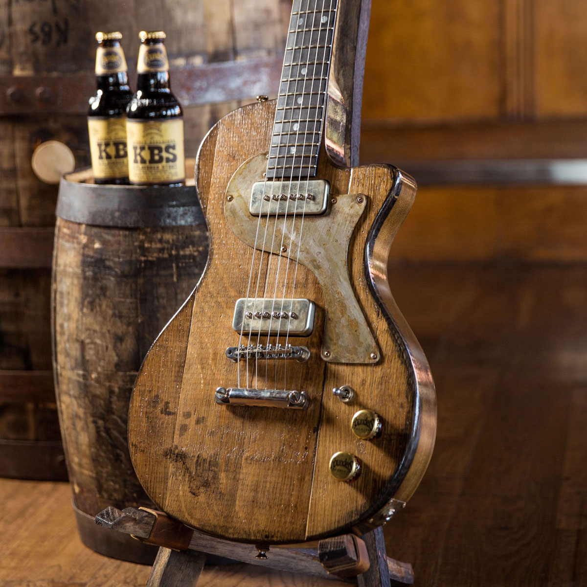 KBS barrel stave guitar with two bottle of KBS stout on barrel next to it