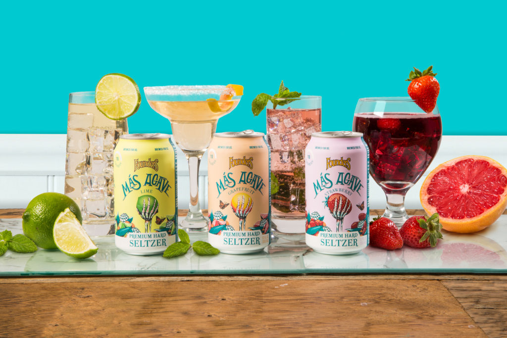 Three cans of Mas Agave Premium Hard Seltzer in front of four different cocktails