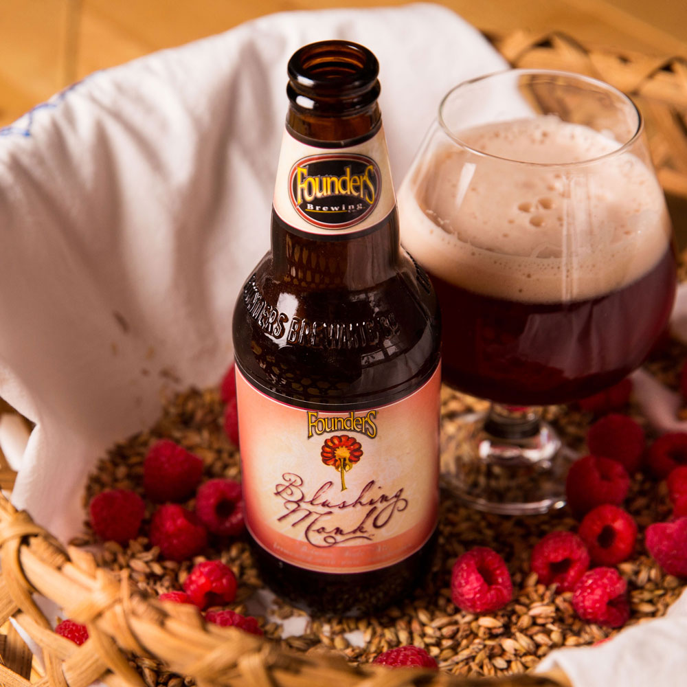 blushing monk bottle next to snifter of blushing monk beer in basket filled with grain and raspberries