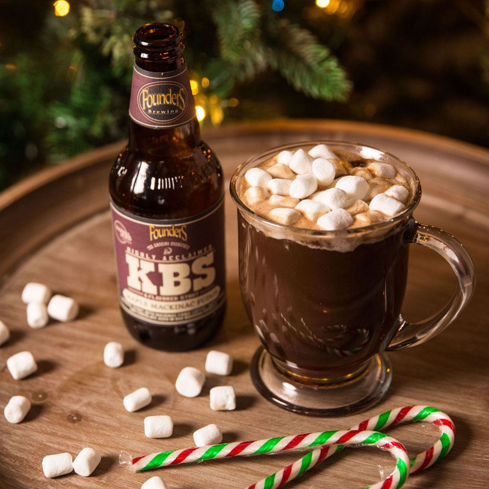 KBS Maple Mackinac Fudge bottle next to cup of hot chocolate with candy canes and marshmallows on table