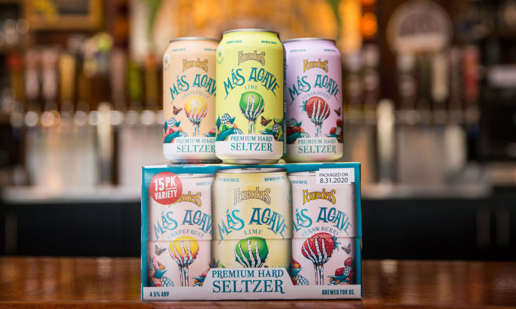 three cans of mas agave premium hard seltzer (lime, grapefruit, strawberry) on top of 15-pack of seltzer