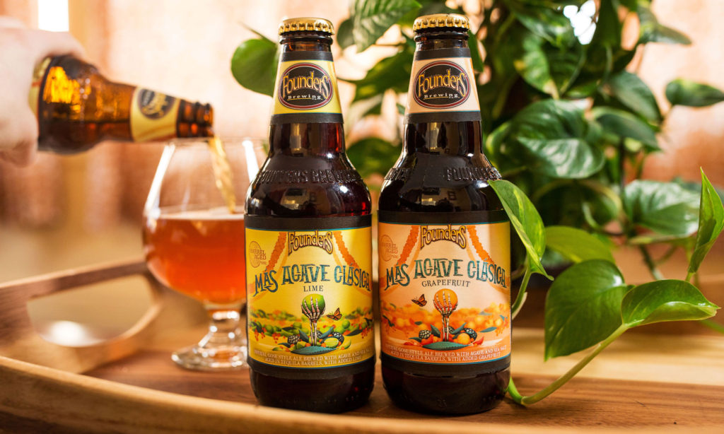 two bottles of mas agave clasica next to snifter pour of the beer