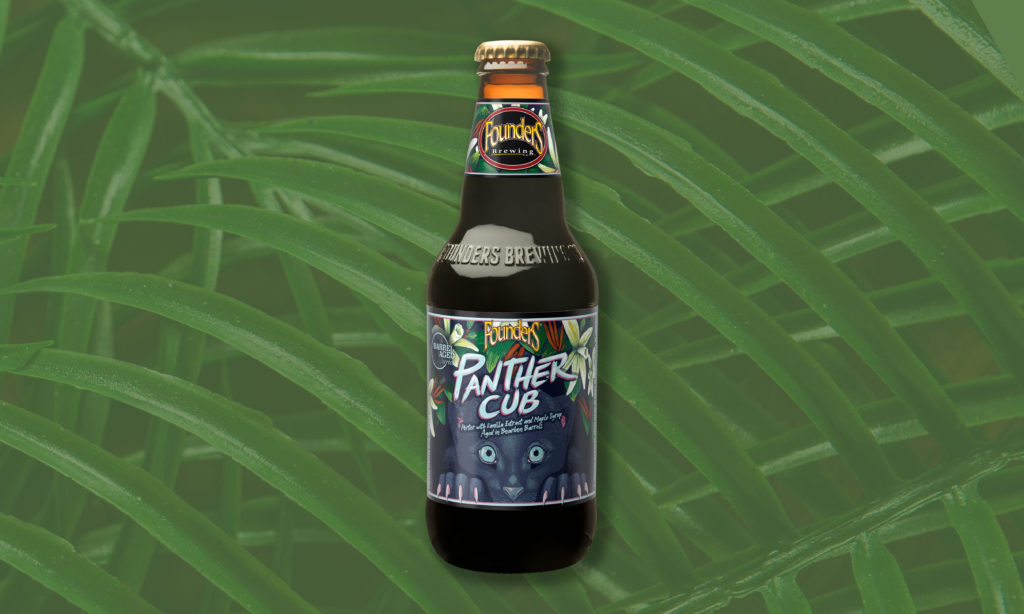 panther cub beer bottle flat lay on top of palm fronds