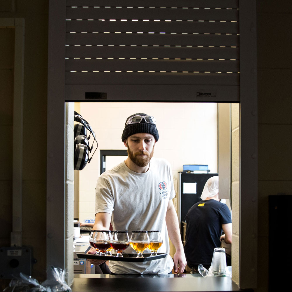 man displaying five snifters on tray and reaching through window